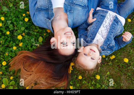 Mother and daughter lying on a green lawn among yellow dandelions. Girls dressed in denim jackets. Spring mood. - Stock Photo