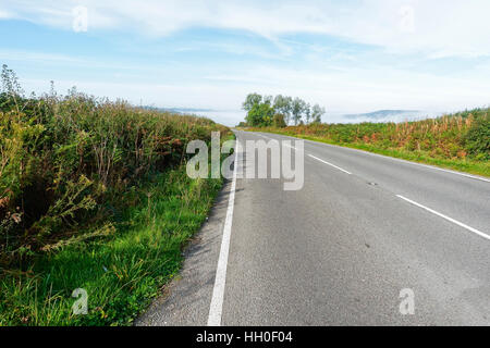 Flanked by grass verges and  hedgerows on either side a deserted country road in Derbyshire, England, disappears - Stock Photo
