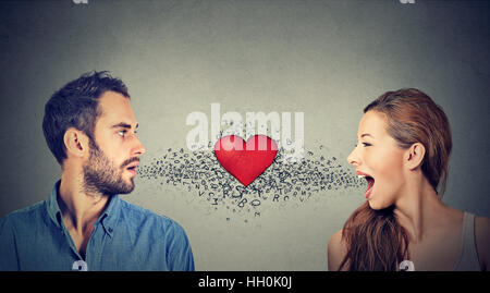Love connection. Man woman talking to each other with red heart in-between and alphabet letters coming out of open - Stock Photo