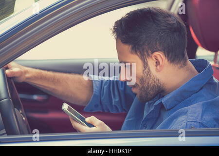 Portrait of handsome young business man using texting on mobile phone while driving a car - Stock Photo