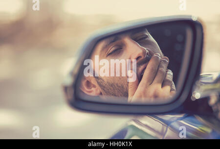Side mirror view reflection sleepy tired fatigued yawning exhausted young man driving his car in traffic after long - Stock Photo