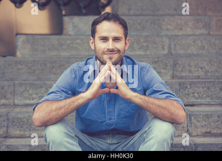 Closeup portrait of happy modern young man smiling sitting outdoors - Stock Photo