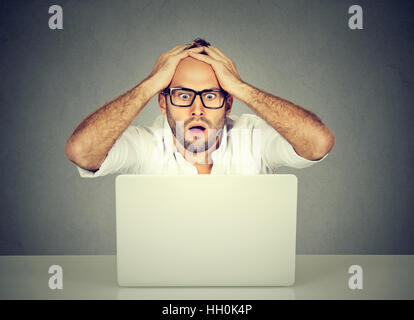 Stressed shocked man looking at his laptop computer - Stock Photo