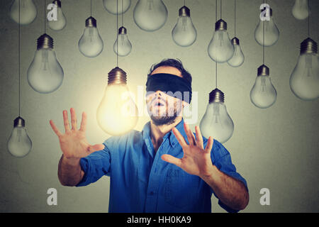 Blindfolded young man walking through lightbulbs searching for bright idea - Stock Photo