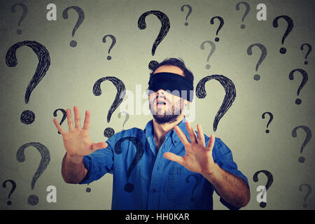 Portrait business man blindfolded stretching his arms out walking through many questions isolated on gray wall background - Stock Photo