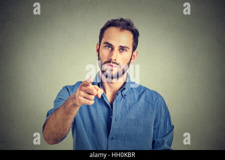 Portrait of a angry young man pointing finger at you camera gesture isolated on gray wall background - Stock Photo