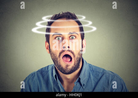 Head is spinning. Surprise astonished man. man looking surprised in disbelief wide open mouth isolated on gray background. - Stock Photo