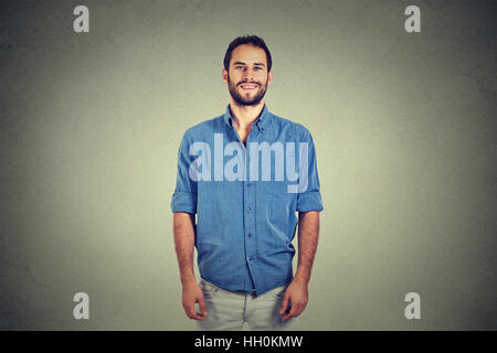 Portrait of a handsome young man smiling isolated against gray wall background - Stock Photo