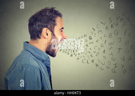Side profile portrait of young angry man screaming with alphabet letters flying out of wide open mouth isolated - Stock Photo