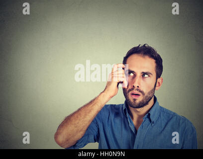 Closeup portrait young man scratching head, thinking deeply about something, looking up, isolated on grey wall background. - Stock Photo