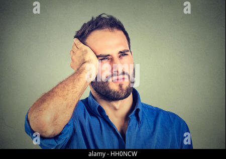 portrait stressed sad handsome young man looking up thinking isolated on gray wall background. Human face expressions - Stock Photo