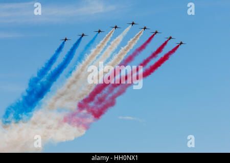 RAF Red Arrows Display Team in flight trailing coloured smoke over Wickenby Airfield - Stock Photo