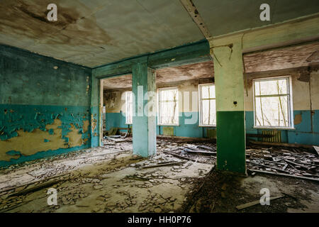 The Ruined Hall Of Abandoned Rural School After Chernobyl Disaster In Evacuation Zone. The Terrible Consequences - Stock Photo