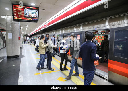 a train pulling in to a Beijing Underground station with passengers waiting - Stock Photo
