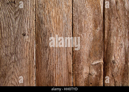 Four vertical very weathered boards inside an old barn door, showing the grain - Stock Photo