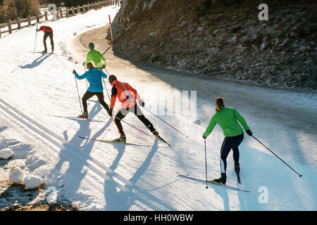 Team of young people cross country skiing training on a winding mountain road in colorful ski clothes - Stock Photo