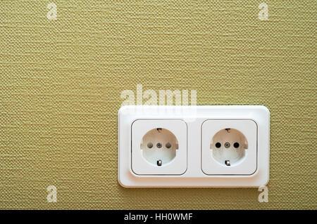 White dual socket on green wall - Stock Photo