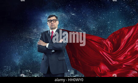Senior businessman dressed as superhero against cityscape background - Stock Photo