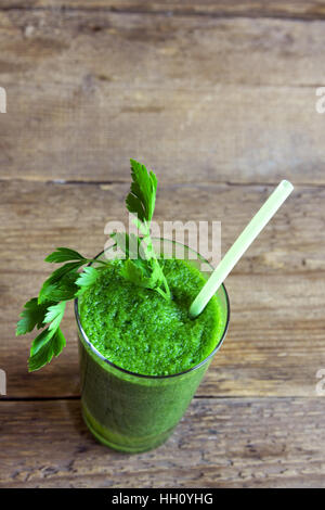 Green smoothie in glass over rustic wooden background with copy space - detox, vegan, vegetarian healthy vegetable - Stock Photo