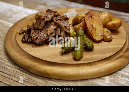 sliced Grilled beefsteak meal on wooden platter with baked potatoes - Stock Photo