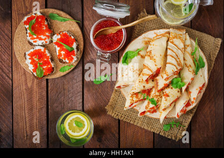 Pancakes with red caviar on plate. Russian cuisine. Maslenitsa - Stock Photo
