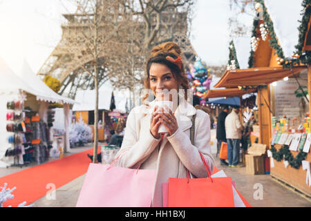 Paris, Woman doing shopping in Christmas market - Stock Photo