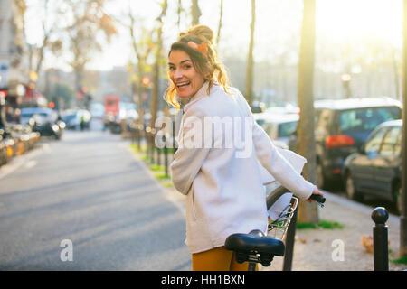Paris, Woman riding a Velib in Paris street - Stock Photo
