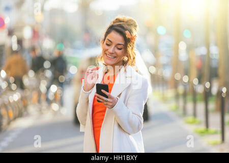 Paris, Woman using smart phone in street - Stock Photo