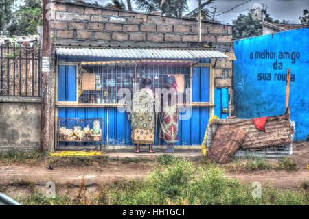 A blue general dealer shop made from tin and brick., with live caged chickens in the front and sarong cladded shoppers. - Stock Photo