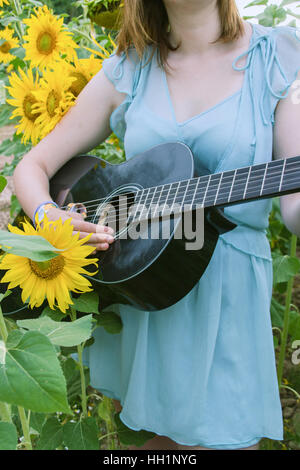 Young woman playing guitar in a field of sunflowers - Stock Photo