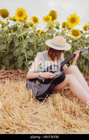Young woman in a field of sunflowers at summer playing her black guitar - Stock Photo