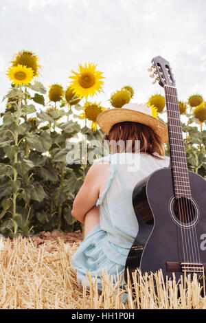 Young woman in summer with her black guitar in front of a lot of sunflowers - Stock Photo