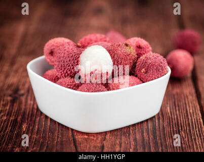 Litchis on rustic wooden background (close-up shot) - Stock Photo