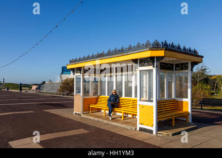 Traditional vintage yellow shelter with wooden bench seats on the promenade at Southsea, Portsmouth, Hampshire, - Stock Photo