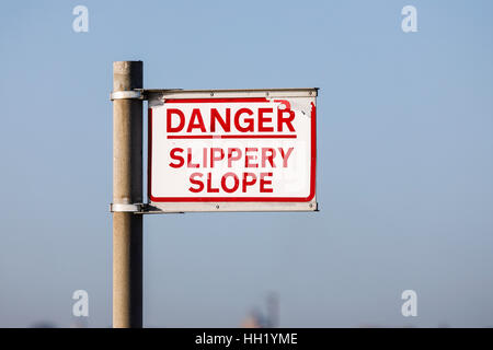 Warning sign 'Danger, slippery slope' by the shore on the seafront at Southsea, Portsmouth, Hampshire, southern - Stock Photo