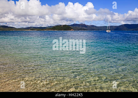 Clean transparent water in coral island lagoon of whitesunday islands. Lonely white yachs anchored off-shore in - Stock Photo