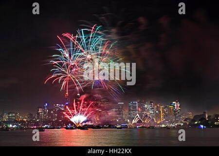 Bright flashy pyrotechnics lights balls in Sydney's sky over city CBD during Australian New Year Eve fireworks reflecting - Stock Photo