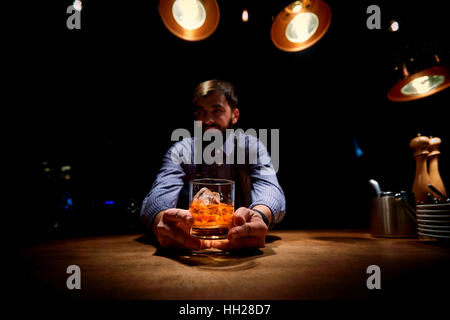 The bartender at  bar with a glass of alcohol in his hands - Stock Photo