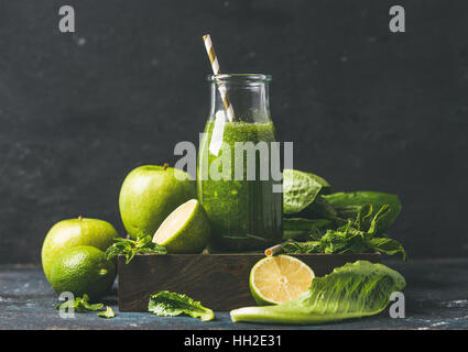 Green smoothie in glass bottle with apple, romaine lettuce, lime - Stock Photo