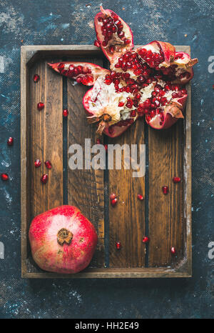 Fresh ripe pomegranates cut in pieces in wooden tray - Stock Photo