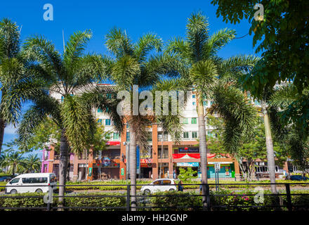 Street scene in Kota Kinabalu, Sabah, Malaysian Borneo with palm trees along the side of the road - Stock Photo