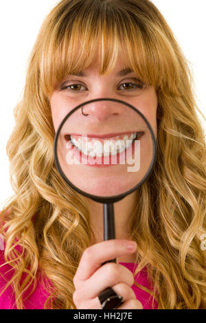 An attractive blonde woman showing off her teeth with a magnifying glass - Stock Photo