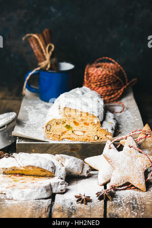 Traditional German Christmas cake Stollen with festive gingerbread cookies - Stock Photo