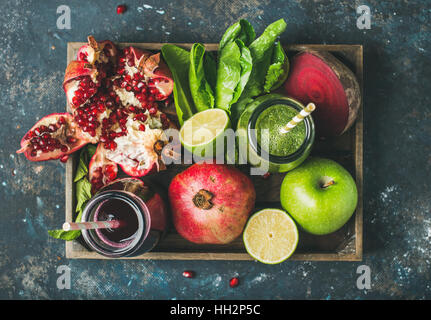 Green, purple fresh juices with fruit, greens, vegetables in tray - Stock Photo
