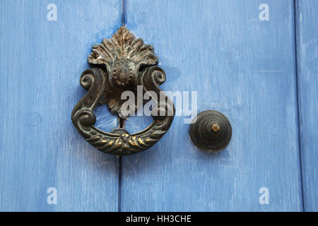 Traditional ornate door handle or knocker against a blue painted wooden door, Cartagena, Colombia. - Stock Photo