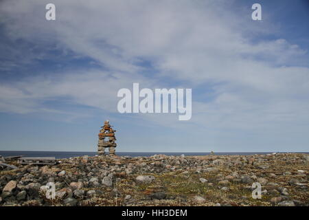 Traditional Inuit landmark (Inukshuk or Inuksuk) near Arviat, Nunavut on the Hudson Bay shoreline - Stock Photo