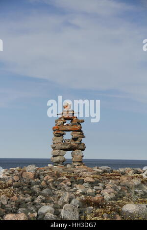 Close-up of traditional Inuit landmark (Inukshuk or Inuksuk) near Arviat, Nunavut on the Hudson Bay shore - Stock Photo