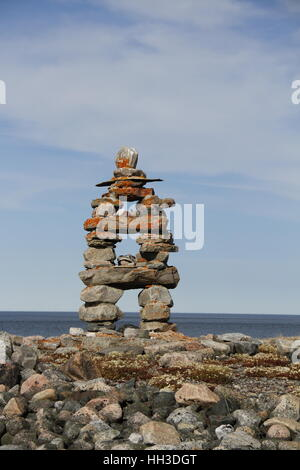 Close-up of traditional Inuit landmark (Inukshuk or Inuksuk) near Arviat, Nunavut on Hudson Bay shore - Stock Photo