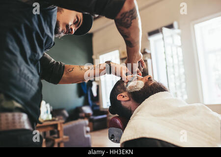 Professional barber shaving customer in his salon. Man getting his beard shaved in a barber shop. - Stock Photo