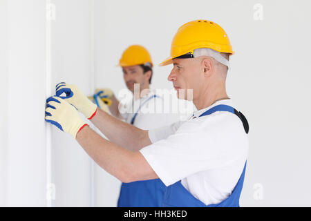 Men in uniform and hardhats measuring wall with tape - Stock Photo